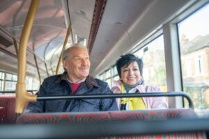 An older man is sitting in a bus next to an older woman who runs a community enterprise and is taking him for a day out. Both people are smiling.