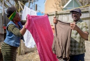 An older man is hanging out washing in a garden and a younger woman is helping him as part of her work as a micro-provider. Both people are smiling.